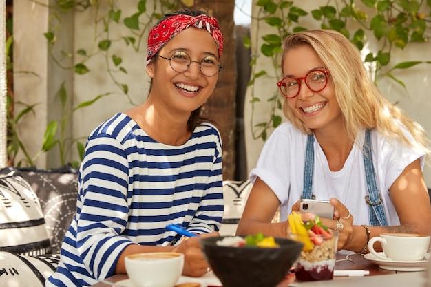 Фотография веселых двух студентов смешанной расы, которые встречаются в кафе для выполнения общей задачи, наслаждаются вкусным блюдом, широко улыбаются, носят оптические очки, болтают по мобильному телефону, записывают упражнения в блокноте, пьют кофе Бесплатные Фотографии