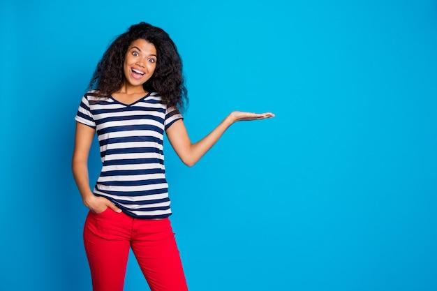 뭔가, 제품 프리젠 테이션을 들고 주머니에 쾌활한 여자 손의 사진, 파란색 벽에 공간을 복사 프리미엄 사진