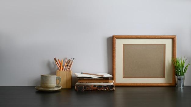 커피 컵, 나무 연필 홀더, 옛날 책, 연필, 액자 및 화분의 사진이 회색 벽과 나무 블랙 테이블에 함께 퍼팅 프리미엄 사진