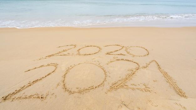 来たる2021年の新年の写真テキストと波のあるビーチでのテキストのレタリングの2020年を去る年 Premium写真