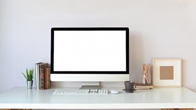 흰색 빈 화면, 책, 화분, 무선 키보드, 마우스, 커피 컵, 연필 홀더 및 흰색 작업 책상에 함께 퍼 팅 액자 스택 컴퓨터 모니터의 사진. 프리미엄 사진