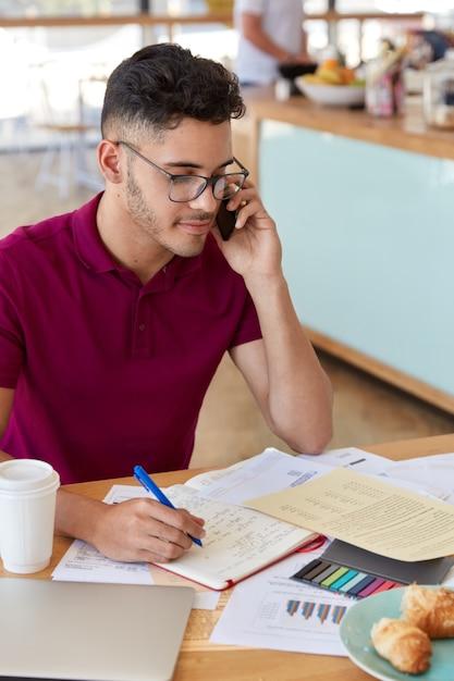 Фотография сосредоточенного мужчины, занятого оформлением документов, держит ручку, имеет модную стрижку, одет в повседневную футболку, общается по мобильному телефону, наслаждается вкусным круассаном с кофе. работа в кафетерии Бесплатные Фотографии