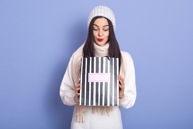 Фото любопытно удивлен молодая самка держа бумажный мешок в обеих руках, глядя внутрь Premium Фотографии