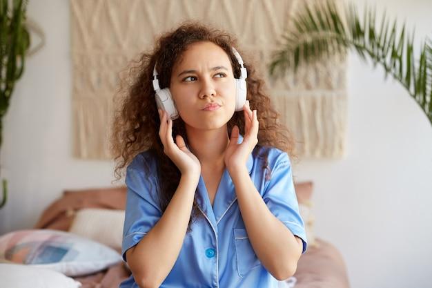 Фотография кудрявой молодой красивой афро-американской леди, слушающей любимую музыку в наушниках, держит наушники, задумчиво смотрит в сторону. Бесплатные Фотографии