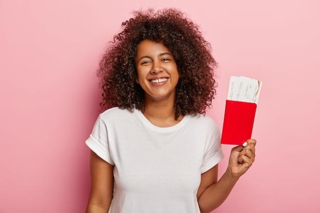 귀여운 어두운 피부의 여성 사진은 티켓과 여권을 보유하고 여름 휴가와 여행을 기뻐하며 그녀의 꿈이 마침내 실현되어 흰색 티셔츠를 입고 비행기를 기다립니다. 여행 컨셉 무료 사진