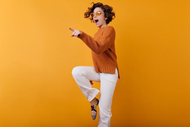미소로 오렌지 공간에서 춤을 추는 모직 스웨터에 검은 머리 소녀의 사진 무료 사진