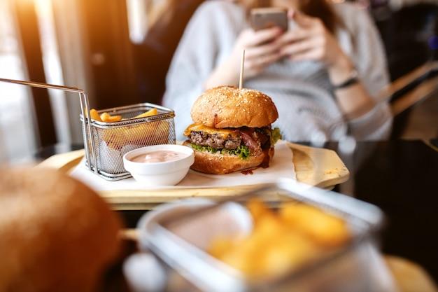 プレート上のおいしいハンバーガー、フライドポテト、ソースの写真。スマートフォンを使用してバックグラウンドで女性。 Premium写真