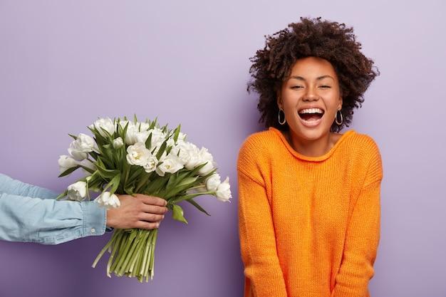 喜んでいるアフリカ系アメリカ人の女性の写真は心から笑い、夫や彼氏から花を手に入れます 無料写真