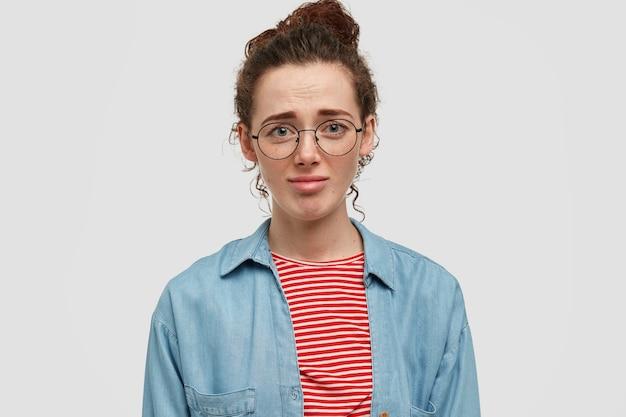 不機嫌なそばかすのあるヨーロッパの女性ティーンエイジャーの写真は、不幸な表情をしていて、彼女の新しい服が好きではなく、カジュアルなシャツと丸い眼鏡をかけ、白い壁に向かってポーズをとっています。顔の表情の概念 無料写真