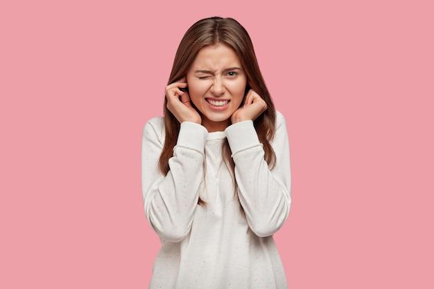 Фотография недовольной женщины затыкает уши от недовольства, не хочет слышать раздражающий звук или шум Бесплатные Фотографии