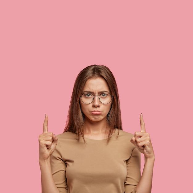 不機嫌な女性が下唇を財布に入れ、表情が不満で不満を持っている写真 無料写真