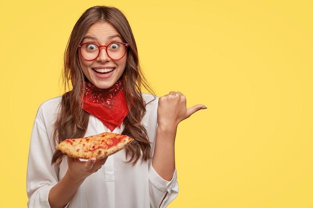 歯を見せる笑顔で感動的な驚きのブルネットの女性の写真、赤いバンダナを身に着け、ピザのスライスを保持し、親指を脇に置いて、広告コンテンツの黄色い壁にモデルを置きます。美味しい料理 無料写真