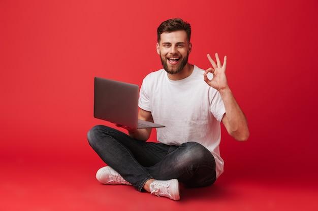 Tシャツとジーンズが足を組んで床に座って、赤い背景に分離されたラップトップを押しながらokサインを示すヨーロッパのうれしそうな男の写真 Premium写真