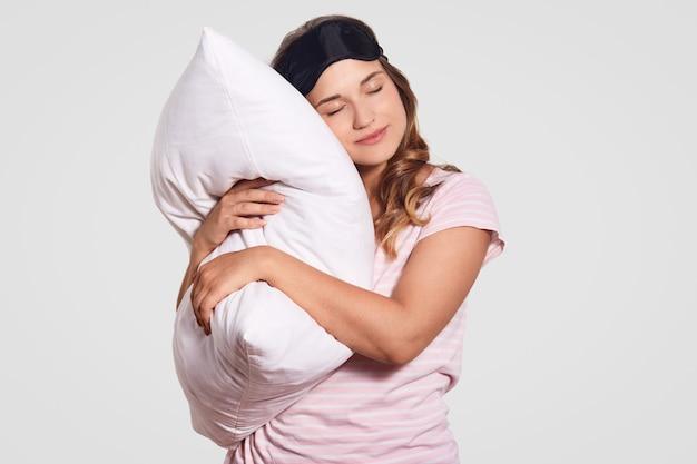 Фотография европейской женщины со здоровой кожей опирается на мягкую подушку, носит пижаму, очки на голове, одевается в белое, имеет сонный взгляд. люди, доброе утро концепция Бесплатные Фотографии