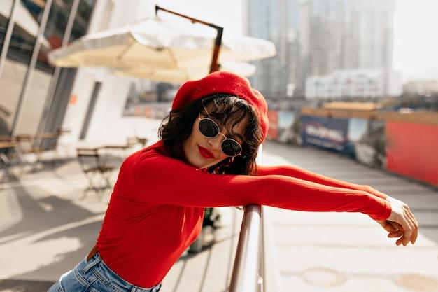 Фотография модной женщины с красивыми каштановыми волосами улыбается Бесплатные Фотографии