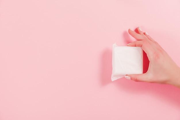 Фото женских рук, держащих гигиеническую прокладку на розовом Premium Фотографии