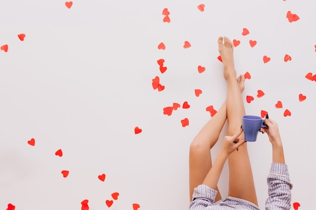 Фото женских ножек на красном конфетти Бесплатные Фотографии