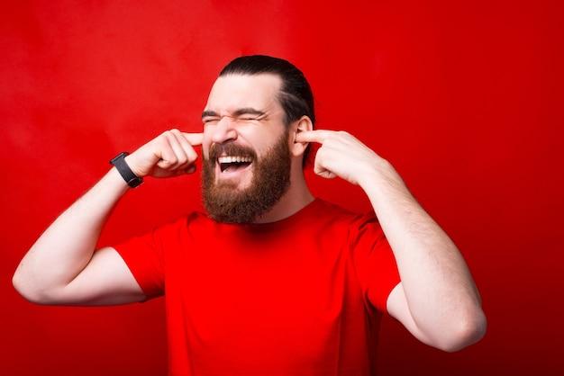 赤い壁に指で耳を閉じている欲求不満のひげを生やした男の写真 Premium写真