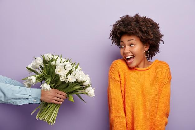 Фотография радостной афро-американской молодой женщины радостно смотрит на букет цветов, который держит мужчина Бесплатные Фотографии