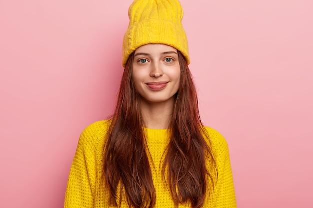잘 생긴 여성 모델의 사진에는 길고 검은 머리카락이 있고 카메라를 쳐다보고 생생한 노란색 모자와 니트 스웨터를 입고 좋은 분위기에 분홍색 배경 위에 격리되어 있습니다. 무료 사진