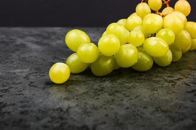 Фото зеленой виноградины на мраморной темной предпосылке. объемный виноград. гроздь зеленого виноградного куста. Premium Фотографии
