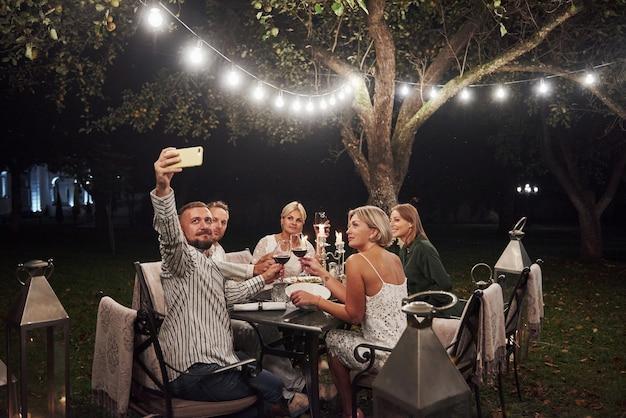男の写真は自分撮りをします。エレガントな服装の友人のグループが豪華なディナーを持っています 無料写真