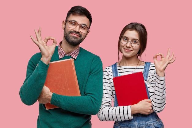 잘 생긴 남자 학생과 그의 여자 동료의 사진은 괜찮은 제스처를 보여주고 무언가에 동의합니다. 무료 사진