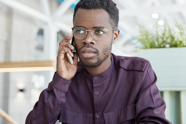 Фотография солидного, серьезного темнокожего мужчины решает во время телефонной консультации, пытается объяснить свою идею, разговаривает со службой поддержки Бесплатные Фотографии