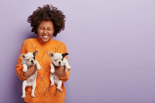 幸せなアフリカ系アメリカ人の女性の写真は、2か月の子犬を抱き、右手で人々に与え、暖かいオレンジ色のセーターを着ています。彼女の最愛の血統の犬との巻き毛の女の子。動物のコミュニケーションの概念 無料写真