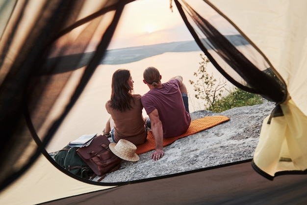 ハイキング旅行中に湖の景色を望むテントに座っている幸せなカップルの写真。 無料写真