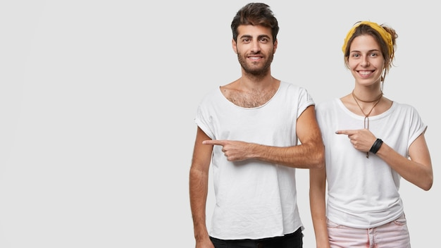 Фотография счастливой, довольной женщины и мужчины, одетых в повседневную одежду, наведите на правую сторону, чтобы показать свободное место для вашей рекламы или рекламы Бесплатные Фотографии