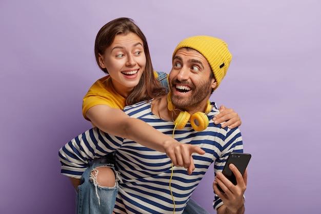 행복한 유럽 커플의 사진은 함께 재미 있고 엔터테인먼트를 위해 현대 기술을 사용합니다. 기쁜 남자가 여자 친구에게 피기 백을주고, 노란 모자와 줄무늬 점퍼를 입고, 셀룰러를 들고, 사진을 보여줍니다. 무료 사진