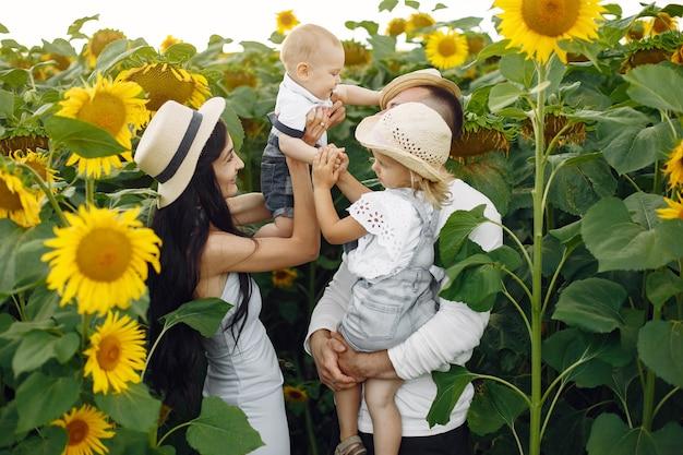幸せな家族の写真。両親と娘。ひまわり畑で一緒に家族。白いシャツの男。 無料写真