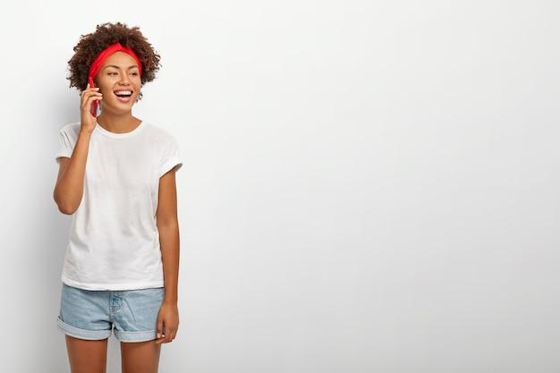 아프로 헤어 스타일, 빨간 머리띠와 함께 행복 한 십 대 소녀의 사진, 멀리 초점을 맞춘 흰색 캐주얼 티셔츠와 진 반바지를 입고, 흰색 배경 위에 절연 친구와 재미있는 전화 대화가 있습니다 무료 사진