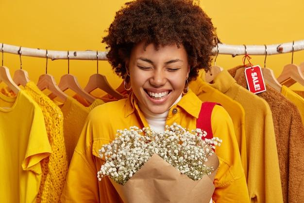 행복한 여자의 사진은 꽃다발을 들고 세련된 노란색 재킷을 입고 넓게 미소 짓고 기뻐하며 옷걸이에 옷 근처에 서 있습니다. 무료 사진