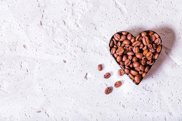ハート型のコーヒー豆の写真はコンクリートの背景にスペースをコピーします。横の写真。上面図 Premium写真