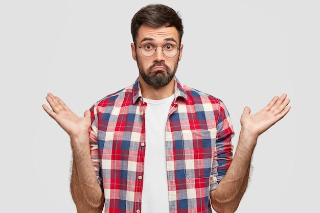 Фотография нерешительного небритого мужчины, неуверенно сжимающего руки, с невежественным выражением лица, сомневающегося, что делать, в клетчатой рубашке стоит у белой стены. люди и концепция замешательства Бесплатные Фотографии