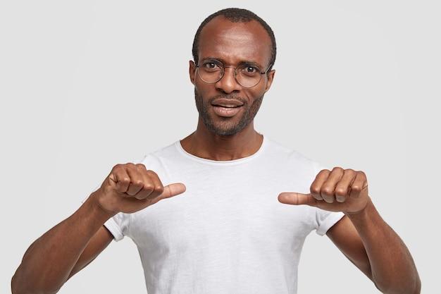 Фото возмущенного небритого афроамериканца показывает пальцами на белую футболку Бесплатные Фотографии