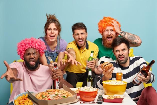 ゲームの結果に不満を持っているイライラしたサッカーファンの写真、カメラを怒って見て、ビールを飲み、ピザ、ハンバーガー、ポップコーンを食べる 無料写真