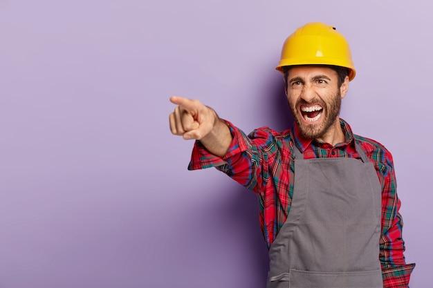Фотография раздраженного рабочего указывает вдаль, недовольного результатом работы, в защитной каске и униформе, кричит от досады, изолирована за фиолетовой стеной. Бесплатные Фотографии