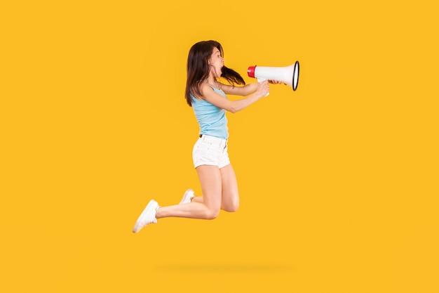 Фотография прыгающей девушки, эмоционально кричащей в мегафон для маркетинговой рекламы, изображение на желтой стене Premium Фотографии
