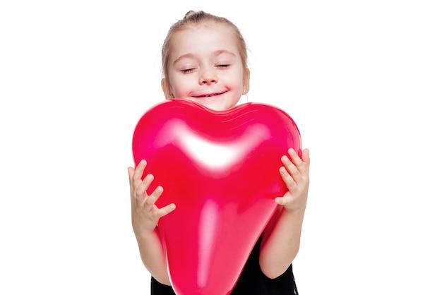 심장 모양의 빨간 풍선을 들고 검은 우아한 드레스에 어린 소녀의 사진 프리미엄 사진