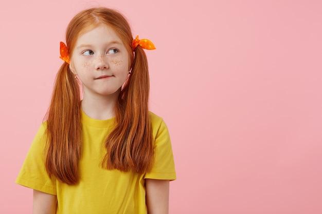 Фотография маленькой думающей рыжеволосой девушки с веснушками с двумя хвостами, смотрит в сторону, трогает щеки, носит желтую футболку, стоит на розовом фоне с копией пространства. Бесплатные Фотографии