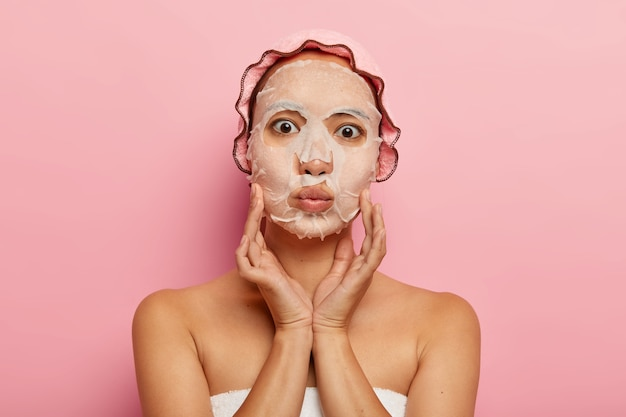 素敵なアジアの女性の写真は、顔に栄養のある保湿紙マスクを付け、頬に優しく触れ、唇を折りたたんで、ピンクのシャワーキャップを着用し、一人で立っています。スキンケアと美容トリートメントのコンセプト 無料写真