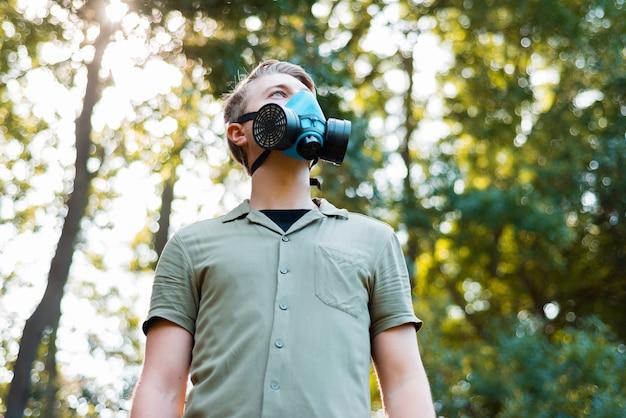 Фотография человека, носящего лицевой респиратор на открытом воздухе в парке и глядя в сторону. Premium Фотографии