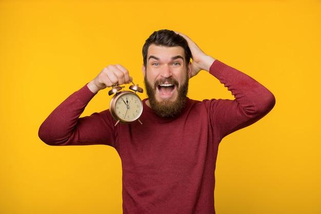 緊張のひげを生やした男、時計を保持し、期限を心配して、黄色の背景の上に立っての写真 Premium写真