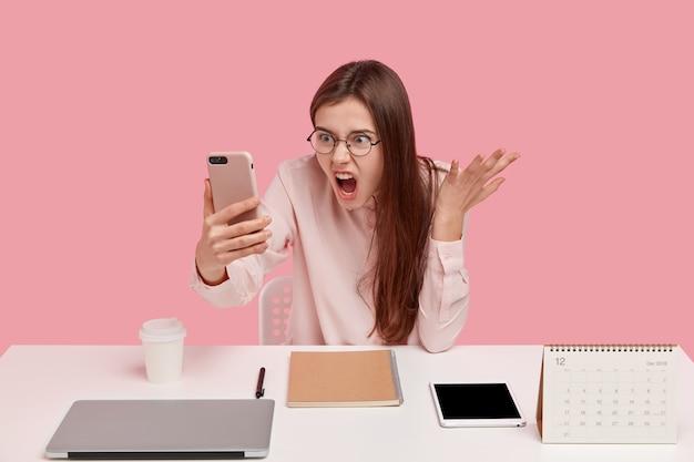 憤慨したイライラした女性の写真は、現代の携帯電話を持って、ビデオ通話をし、同僚と議論し、職場でポーズをとる 無料写真