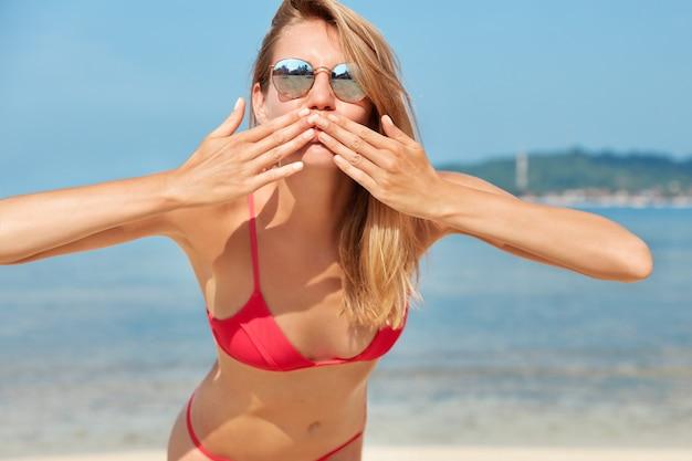トレンディな色合いで満足している女性観光客の写真、カメラでエアキスを吹く、青い地平線に対するオーシャンビューに対するポーズ、完璧なスリムなボディ、海岸線での再現。人、夏、残り 無料写真