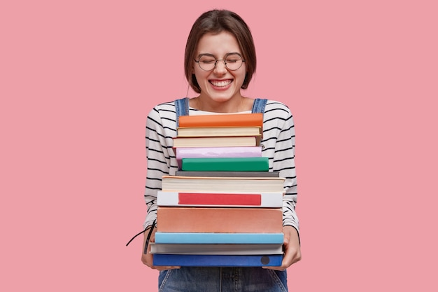 기쁘게 십대 소녀의 사진은 교과서의 힙을 보유하고 있으며, 높은 정신으로 데님 바지를 입고 분홍색 배경에 포즈를 취합니다. 무료 사진