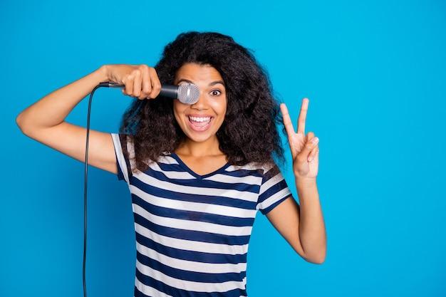 마이크로 눈을 덮고있는 V 기호를 보여주는 긍정적 인 여성의 사진 프리미엄 사진
